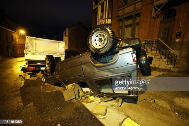 An overturned car is seen in Belgium's Dinant after heavy rain and floods caused major damage on July 24, 2021.