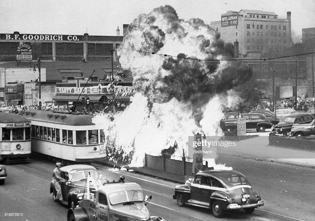 An overturned car, owned by a Negro, blows up and showers burning gasoline on a passenger-packed trolley car in Detroit, during the race riot which still continues in spite of armed troops ordered to assist police. A 'state of emergency' has been declared in hopes of quelling the fierce mob fighting between Negroes and whites.