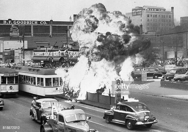 An overturned car owned by a Negro blows up and showers burning gasoline on a passengerpacked trolley car in Detroit during the race riot which still...