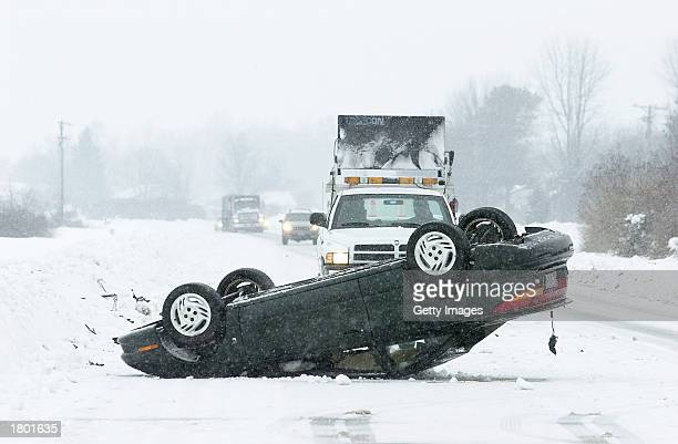 An overturned car sits on a snowcovered highway February 18 2003 near Milford Delaware A State of Emergency was declared for the entire state after a...
