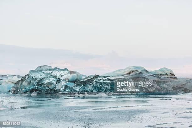 An overturned iceberg glistens bright blue in Jokulsarlon glacier lagoon on January 2 2017 in Reykjavik Iceland