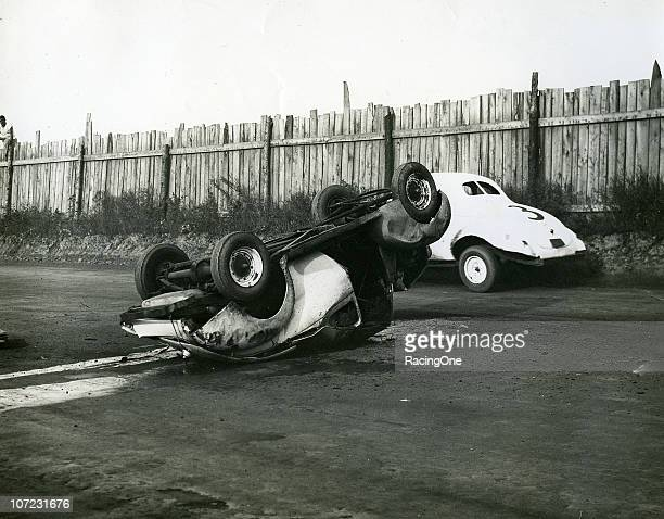 An overturned modified stock car gets passed by fellow driver Johnny Rogers at North Wilkesboro Speedway There were no injuries