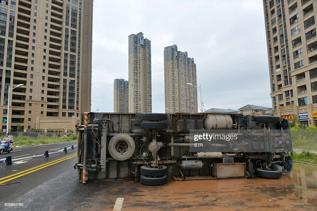 An overturned truck is seen on a street in Xiamen, China's eastern Fujian province, after Typhoon Meranti made landfall on September 15, 2016. Typhoon Meranti made landfall in Fujian early September 15 with winds up to 230kph, knocking out electricity in some areas and causing rail delays. / AFP / STR / China OUT
