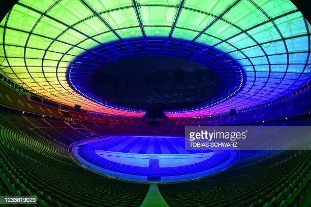 An overview picture shows from inside the Olympic stadium as it is illuminated with the Rainbow colours, in Berlin, eastern Germany, on June 23,...