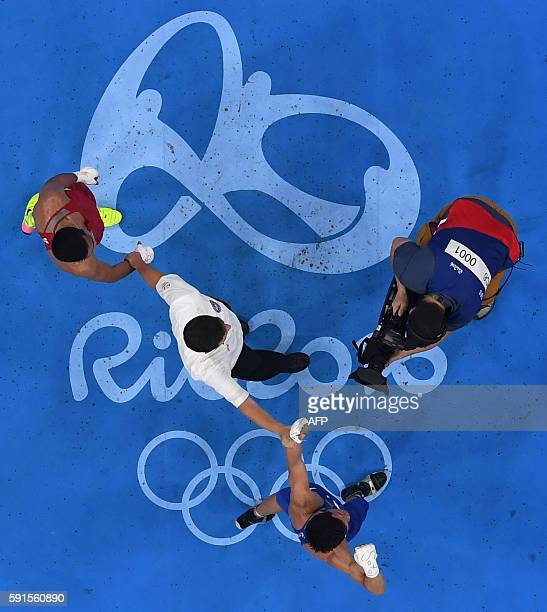 An overview shows a cameraman filming as Uzbekistan's Shakhram Giyasov and Kazakhstan's Daniyar Yeleussinov wait for the results during the Men's...