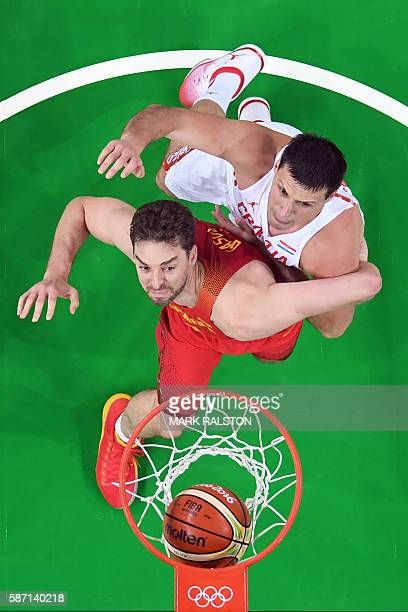 An overview shows Croatia's centre Darko Planinic scoring despite Spain's centre Pau Gasol during a Men's round Group B basketball match between...