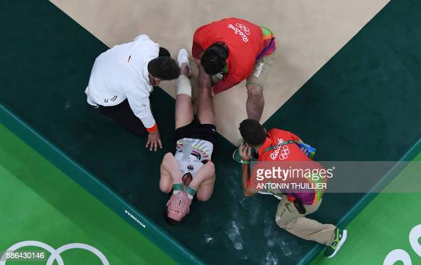 An overview shows Germany's Andreas Toba reacting after being injured while competing in the qualifying for the men's floor exercise event of the...