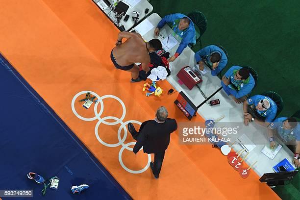 An overview shows Mongolia's Mandakhnaran Ganzorig's coach reacting after the judges announced that Uzbekistan's Ikhtiyor Navruzov won following a...