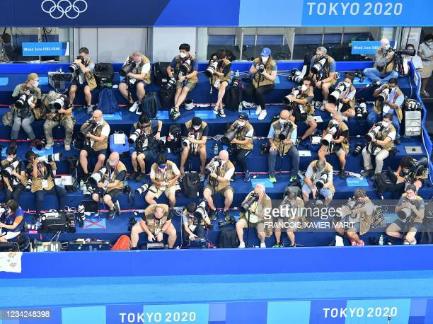 An overview shows photographers working at a swimming event during the Tokyo 2020 Olympic Games at the Tokyo Aquatics Centre in Tokyo on July 28,...