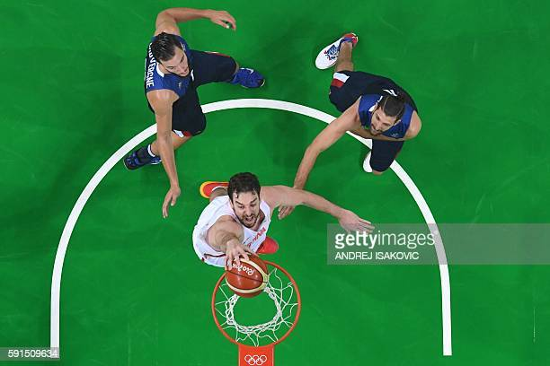 TOPSHOT An overview shows Spain's centre Pau Gasol score past France's power forward Joffrey Lauvergne and France's point guard Antoine Diot during a...