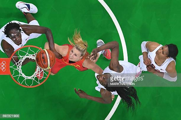 An overview shows USA's centre Tina Charles Spain's power forward Laura Gil USA's centre Sylvia Fowles and USA's forward Maya Moore eye a rebound...
