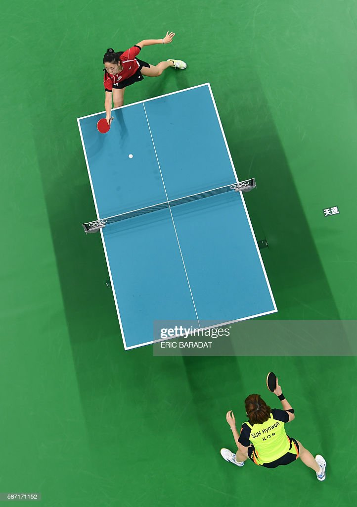 An overview shows USA's Lily Zhang (top) playing against South Korea's Suh Hyowon in their women's singles qualification round table tennis match at the Riocentro venue during the Rio 2016 Olympic Games in Rio de Janeiro on August 8, 2016. / AFP / POOL / Eric BARADAT