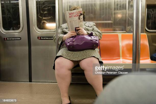 """An overweight female commuter is reading an article entitled """"Why I love my mom"""" on a late-evening New York City subway train."""