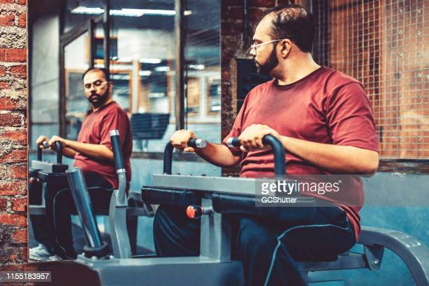 an overweight man at a gym using exercising machine while looking at the mirror - centro benessere struttura ricreativa foto e immagini stock