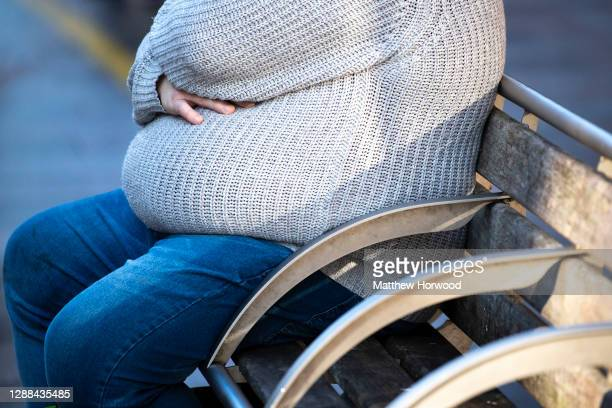 An overweight man sits on a bench on November 27, 2020 in Cardiff, Wales.