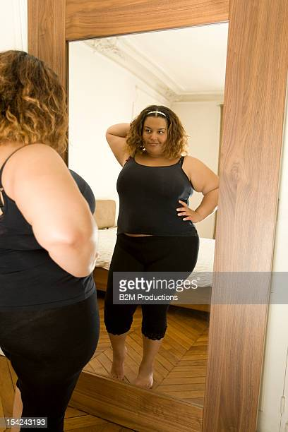 an overweight woman looking in the mirror - full length mirror stock photos and pictures