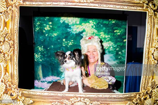 An owner dressed in costume sits for a photograph with her Papillion dog during the annual Meet the Breed event ahead of the 141st Westminster Kennel...