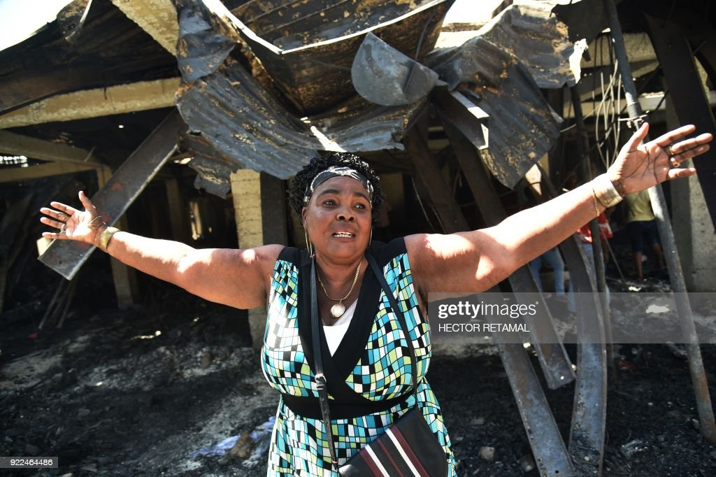 An owner grieves as she inspects her lost shop in the worse-hit area at the Nan Gerit Market in Port-au-Prince on February 21, 2018. A fire gutted the textiles market in Haiti's capital on February 18. /