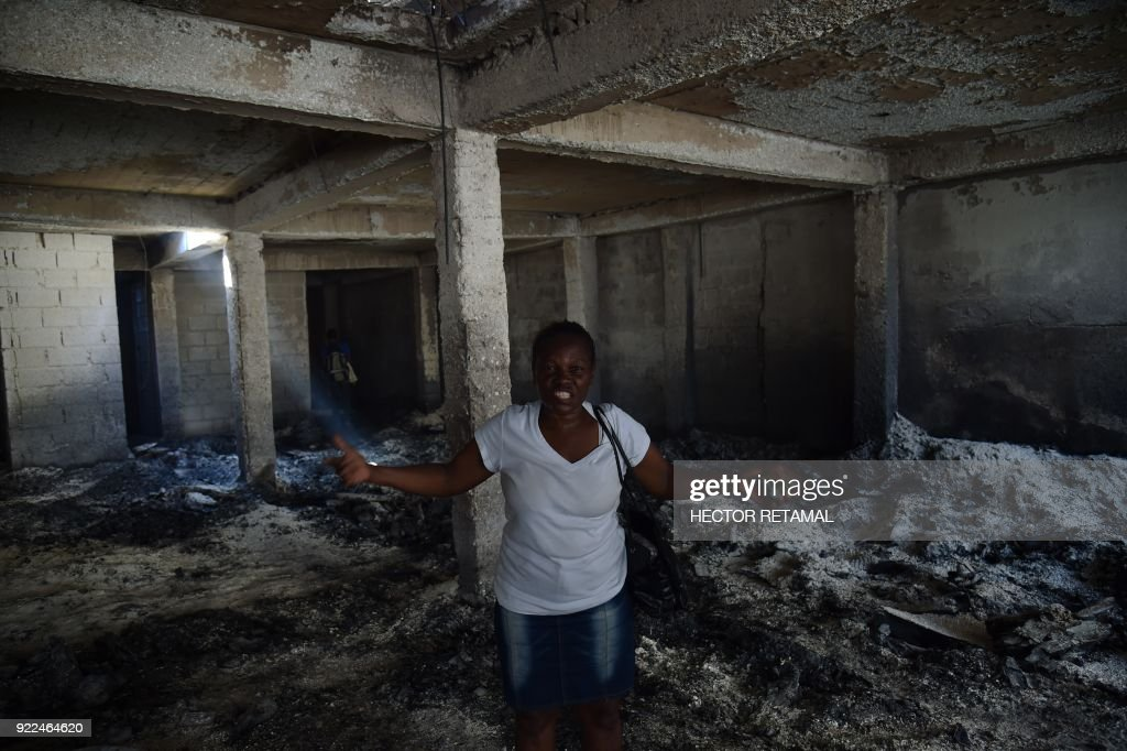 An owner grieves as she inspects her lost shop in the worse-hit area at the Nan Gerit Market in Port-au-Prince on February 21, 2018