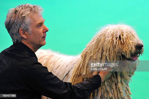 An owner holds his Komondor on the fourth day of Crufts dog show in Birmingham central England on March 10 2013 The annual event sees dog breeders...