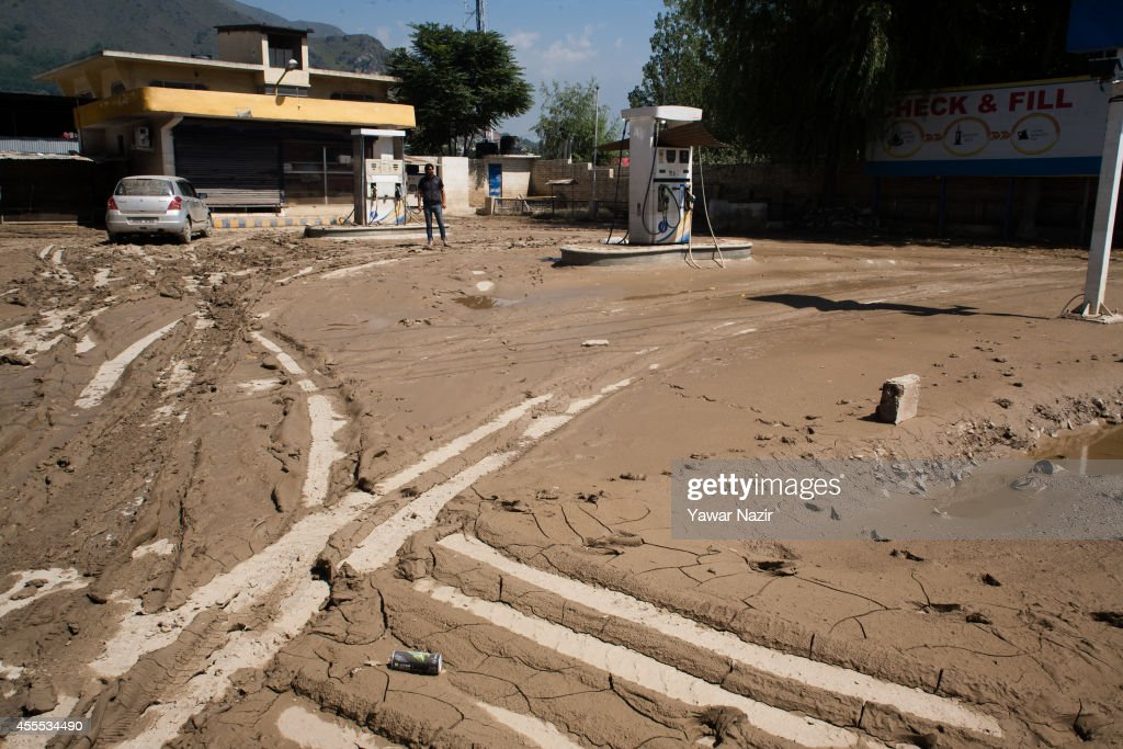 An owner looks at his silt covered gas station after the flood waters receded on September 16, 2014 in Srinagar, the summer capital of Indian administered Kashmir, India. Nearly 200,000 people are still marooned in the areas of the Kashmir Valley submerged in flood waters. The floods in the Himalayan region of Kashmir were believed to be the worst in decades with over 200 dead. Health experts are worried over the stagnant waters and floating carcasses of livestock could create conditions for serious outbreaks of disease.