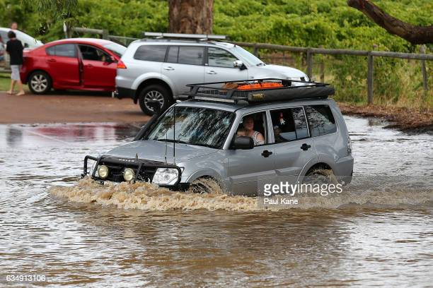 An owner of a 4WD vehicle drives in flood water next to Maali bridge as flood waters rise in the Swan River on February 12 2017 in the suburb of...