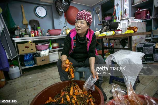 An owner of traditional Korean food store Park Jeongsook prepares kimchi as she watches the news reporting on South Korean President Park Geunhye's...