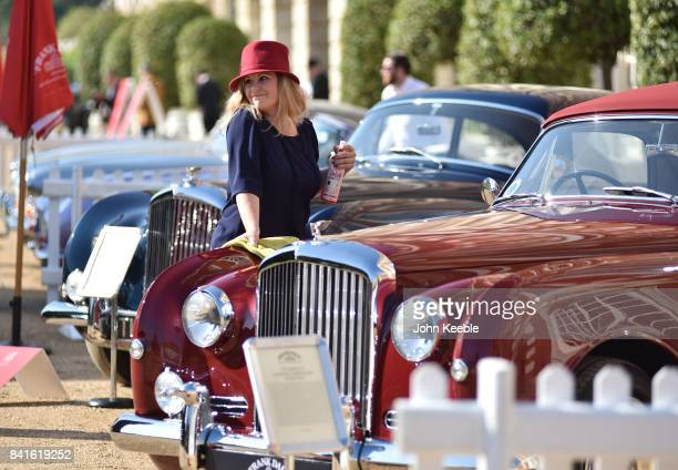 An owner polishes her car on display at the Concours de Elegance at Hampton Court Palace on September 1, 2017 in London, England. The show brings...