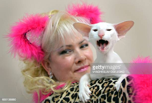 An owner poses with her Oriental Shorthair cat during the International cat exhibition in Bishkek on March 19, 2017. / AFP PHOTO / VYACHESLAV OSELEDKO