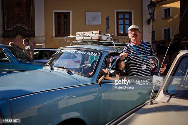 An owner stands by his Trabantbrand car as he arrives at a commemoration event to the 25th anniversary of refugee exodus from communist East Germany...