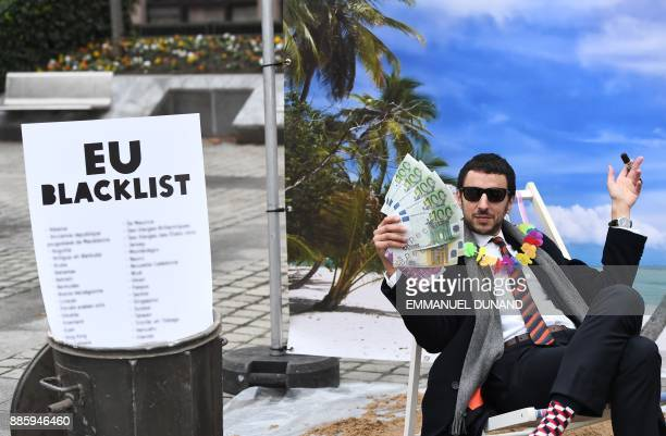 An Oxfam activist stages a satirical streetplay mimicking a wealthy person hidding his money in a tax haven on December 5 2017 near the European...