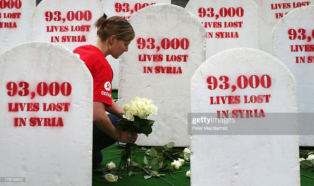 An Oxfam worker places roses amongst rows of gravestones symbolising the 93,00 people killed in Syria on June 17, 2013 in Belfast, Northern Ireland. The two day G8 summit, hosted by UK Prime Minister David Cameron, is being held in Northern Ireland for the first time. Leaders from the G8 nations have gathered to discuss numerous topics with the situation in Syria expected to dominate the talks.
