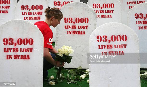 An Oxfam worker places roses amongst rows of gravestones symbolising the 93,00 people killed in Syria on June 17, 2013 in Belfast, Northern Ireland....