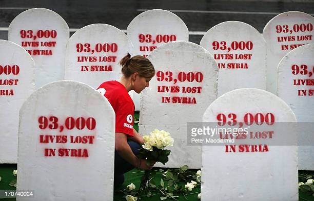 An Oxfam worker places roses amongst rows of gravestones symbolising the 9300 people killed in Syria on June 17 2013 in Belfast Northern Ireland The...