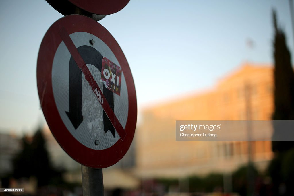 An 'Oxi' (No) sticker from lastweeks referendum adorns a No U turns sign outside the Greek parliament as protesters to demonstrate against austerity after an agreement for a third bailout with eurozone leaders on July 13, 2015 in Athens, Greece. The bailout is conditional on Greece passing agreed reforms in parliament by Wednesday which includes streamlining pensions and rasing more raise tax revenue.