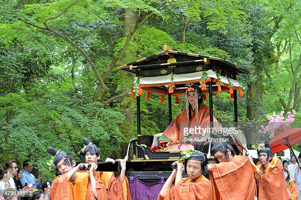 An 'Oyoyo' float carrying the 'Saiodai' queen wearing 'junihitoe' the layered formal kimono of Heian Period court ladies march on during the Aoi...