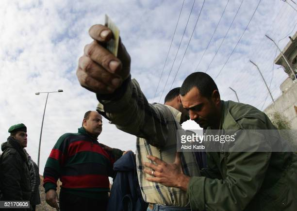 An Palestinian security check Palestinian workers as they arrive at Erez Chickpoint to enter the Erez industrial zone February 10 2005 in northern...