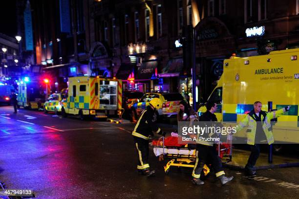 An person injured during a roof collapse at the Apollo Theatre is stretchered away by members of the emergency services on December 19 2013 in London...