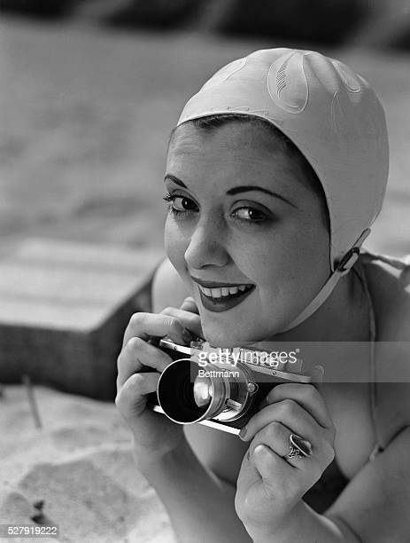 An photograph of a girl in a bathing suit with a miniature camera Model Virginia Cruzon Undated photograph