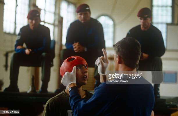 An physical education instructor tests an army recruit for concussion after a bout of Milling a test of aggression that recruits must pass before...