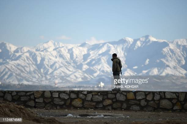 TOPSHOT An policeman keeps watch as Afghan civil society activists celebrate Valentine's Day at Wazir Akbar Khan hilltop in Kabul on February 14 2019...