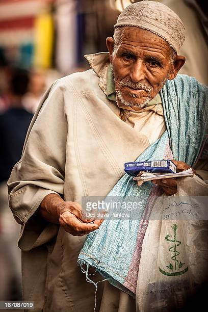 An poor Moroccan old man /peasant/walked the streets of Marrakech, Morocco in early afternoon of September and holding coins in his hand. He is...