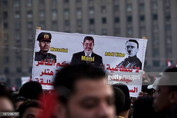 An poster likening Egyptian President Mohammed Morsi to Benito Mussolini and Adolf Hitler is held above the heads of demonstrators in Tahrir Square...