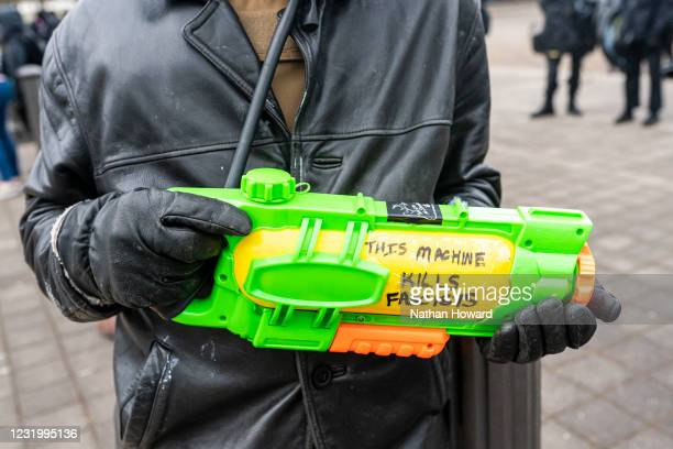 An protester displays a water gun filled with an unidenfied substance on March 28, 2021 in Salem, Oregon. The protesters clashed with occupants of...