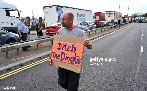 An protester holds a placard as he walks past a line of vehicles, brought to a standstill by an anti-immigration protest in Dover on the south-east...