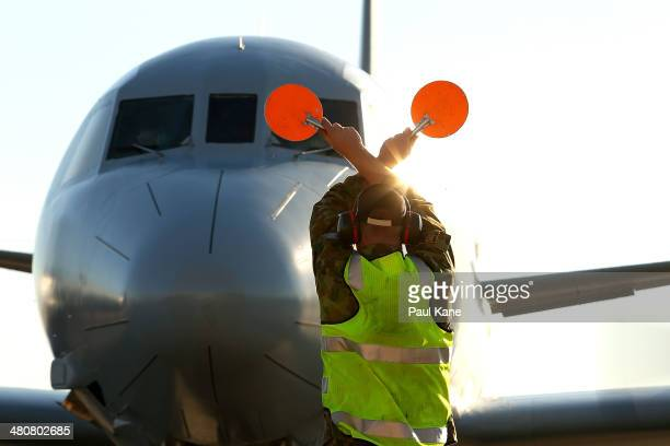 An RAAF signalman directs an AP-3C Orion for parking on the apron after returning from a search mission for MH370 debris at RAAF Base Pearce on March...