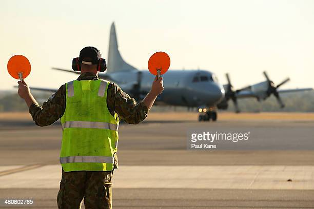 An RAAF signalman directs an AP3C Orion for parking on the apron after returning from a search mission for MH370 debris at RAAF Base Pearce on March...