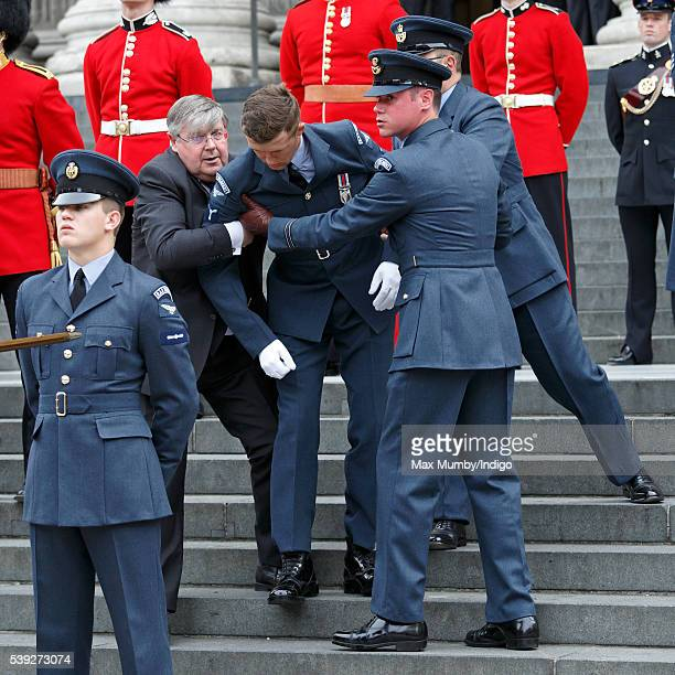 An RAF Airman forming part of the guard of honour is helped to his feet after collapsing at a national service of thanksgiving to mark Queen...