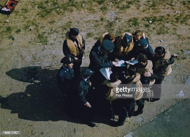 An RAF bomber crew checking their briefing documents World War II circa 1943