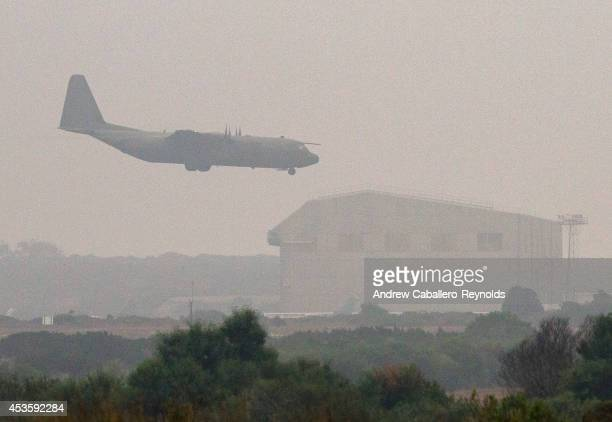 An RAF C130 transport plane lands in heavy fog early in the morning on August 14 2014 in Akrotiri CyprusRoyal Air Force C130 Hercules military...